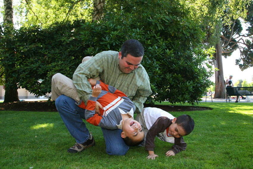 Boys playing with dad in grass