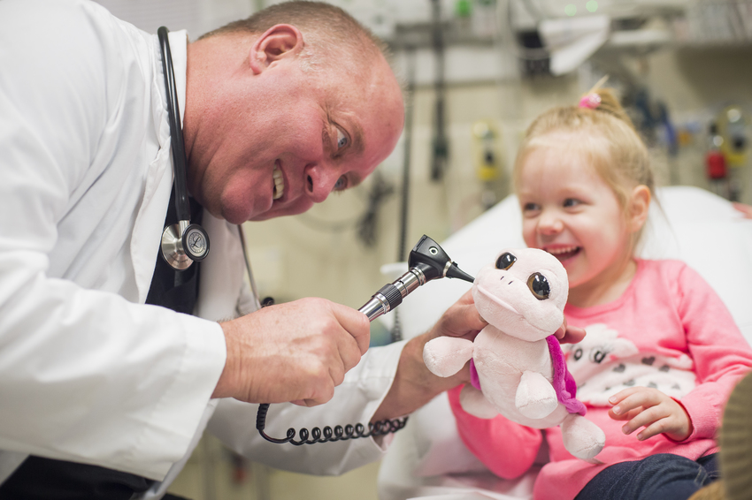 Doctor Making Girl Laugh with Stuffed Animal